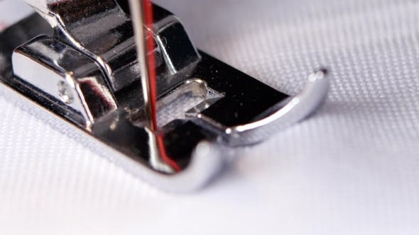 Thumbnail for Electric Sewing Machine Makes a Red Thread Stitch.