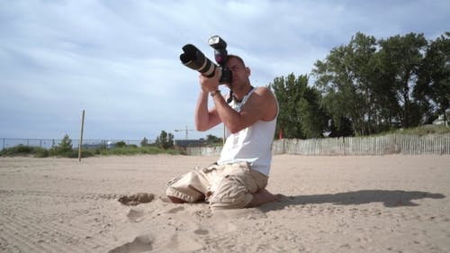 Photographer in Action. Professional Photographer Outdoor. Photographer Beach
