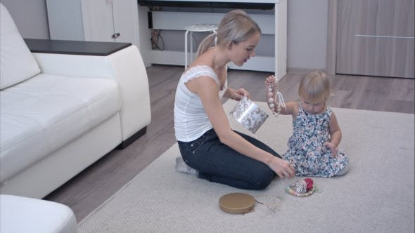 Mother and Daughter Happily Playing with Female Accessories