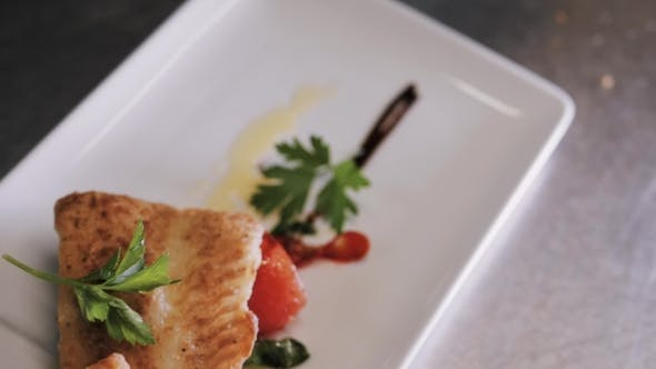 Thumbnail for Healthy Food Concept: Chief Serving Hot Baked Fish Piece Over White Plate
