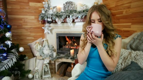 Cover Image for Woman Hands Holding Coffee or Tea Cup Against Cozy Fireplace in Winter. Girl Is Having Hot Drink