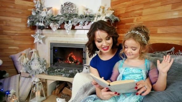 Thumbnail for Mother and Daughter Read a Book, Family Reading a Christmas Story While Sitting By the Fireplace and