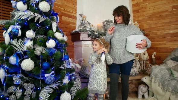 Mother and Daughter Are Preparing for the New Year Holiday, Family Decorating a Christmas Tree