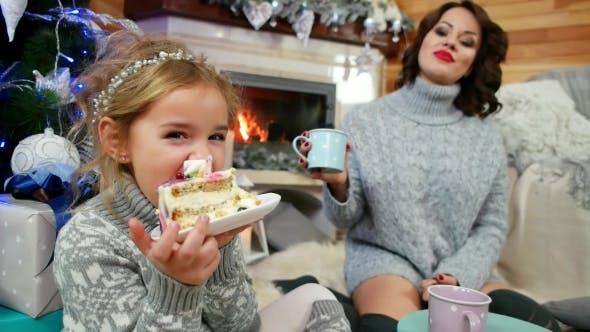 Thumbnail for Mama und Tochter genießen verbringen Zeit zusammen, Mädchen mit Vergnügen Essen ein großes Stück Kuchen bei