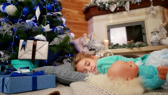 Thumbnail for Little Cute Girl Hugging a Doll During Sleep, The Child Sleeps Near a Christmas Tree, Sweet Sleep in