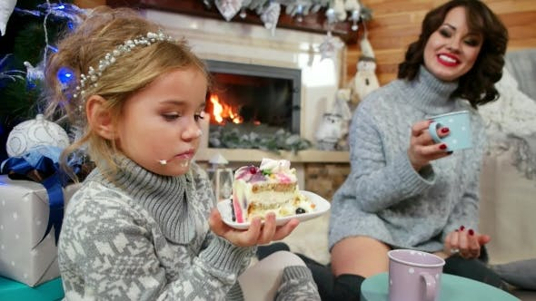 Thumbnail for Girl Eating a Large Piece of Cake at The Christmas Tree, Mom and Daughter, Family By the Fireplace