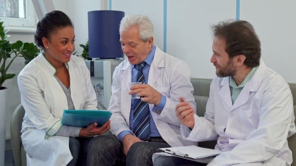Thumbnail for Medical Team of Three Doctors Sits on the Couch at the Hospital