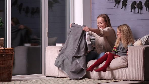 Thumbnail for Mother and Daughter Wrapping in Blanket on Couch