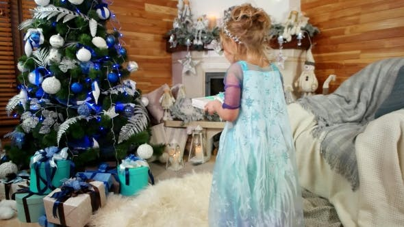 Cover Image for Girl Lays Down Gift Under the Christmas Tree, Child Is Preparing a New Year Surprise for Parents