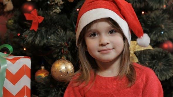 Little Girl Poses in Santa's Hat