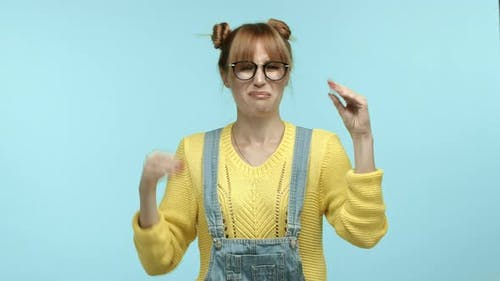 Annoyed Hipster Woman in Glasses and Overalls Mocking Someone Talking Too Much Showing Blah Blah