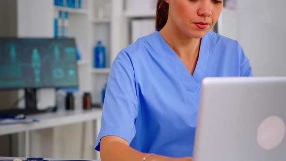 Portrait of Nurse Looking at Camera Smiling After Typing on Laptop Sitting