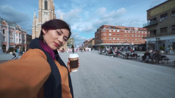 Cover Image for Woman Tourist Taking Selfie on Phone with Coffee
