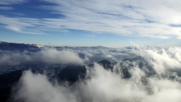 Aerial Drone Flying Over Mountains and Clouds