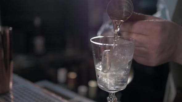 Thumbnail for Bartender Is Making Cocktail at Bar Counter, Adding Some Bitter in the Shaker