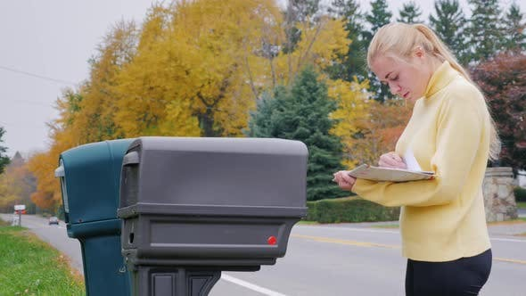 Caucasian Woman Takes the Mail From the Mailbox - Countryside in USA