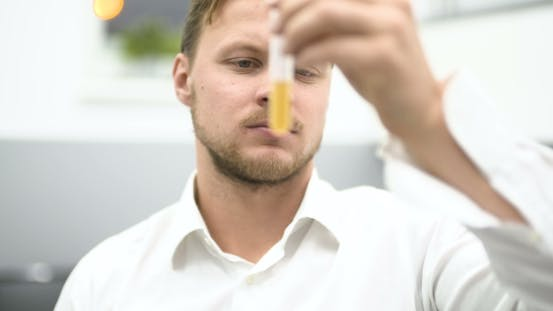 Thumbnail for Scientist in Laboratory Examining Liquid in Glass Beaker.
