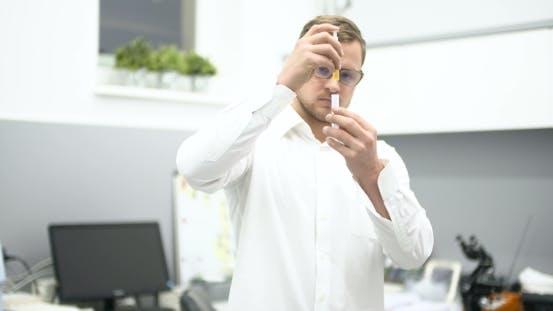 Thumbnail for Scientist in Laboratory Examining Liquid in Glass Beaker.