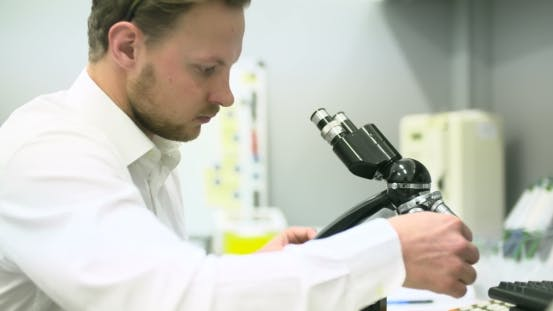 Thumbnail for Scientist Is Looking Through Microscope and Writing Data on Tablet.