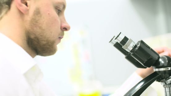 Cover Image for Scientist Is Looking Through Microscope and Writing Data on Tablet.