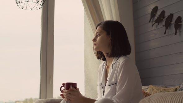 Thumbnail for Attractive Girl Looks Out the Window at Cosy Flat