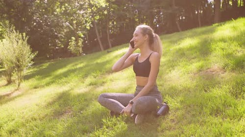 Cheerful Blonde Girl Talking on Cellphone, Resting on Grass