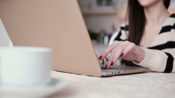 Thumbnail for Beautiful Young Brunette Woman Uses Laptop in a Bright Dining. Slider To the Right