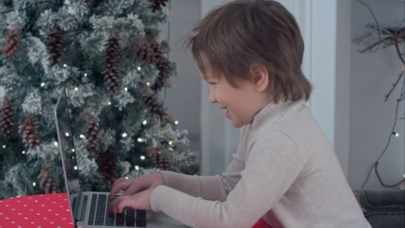 Thumbnail for Smiling Little Boy Typing Letter To Santa Claus on a Laptop Near the Christmas Tree