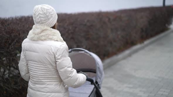 Junge Mutter zu Fuß mit einem Kind im Kinderwagen. Herbstsaison