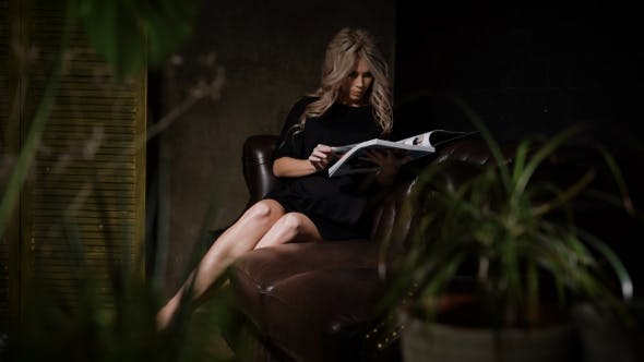 Thumbnail for Beautiful Pregnant Blonde in Black Dress Sitting in the Dark Room on the Big Brown Leather Sofa with