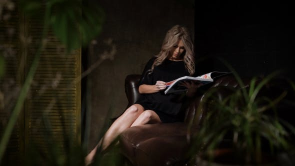 Thumbnail for Pregnant Woman in Beautiful Black Dress Sitting in the Dark Room on the Big Brown Leather Sofa with