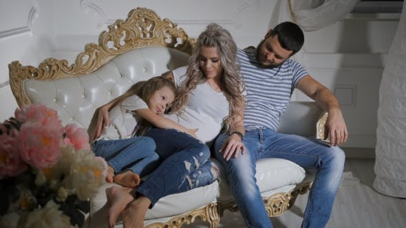 Thumbnail for Father, Pregnant Mother and Little Daughter Are Sitting Together on the Couch and Hugging. Daughter