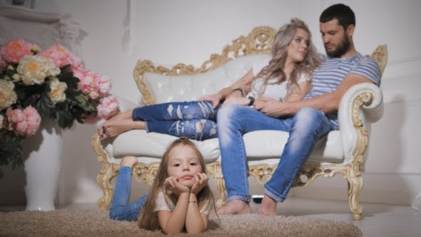Thumbnail for of Happy Family, Expecting New Baby, with Little Daughter in the Foreground, Lying on the Carpet