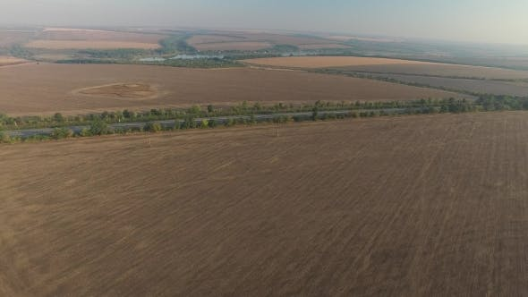 Thumbnail for Aerial View Tilled Field Near the Highway with Cars