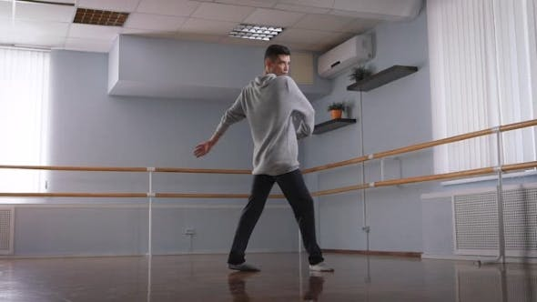 Thumbnail for Handsome Male Dancer in Grey Pullover and Black Trousers Dancing in the Center of the Classroom