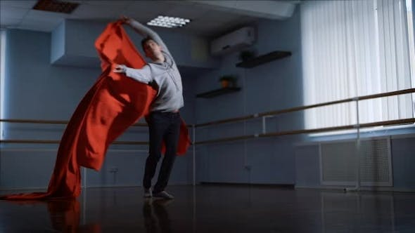 Thumbnail for Professional Dancer Finishes His Dance of Beautiful Wave of Red Cloth in Front of Him
