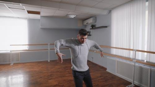 Le professeur de danse dans la salle des répétitions. Il fait les mouvements lents et lisses, travaillant ainsi