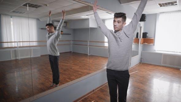 Thumbnail for Junge Schüler der Tanzschule, die in der Nähe des Spiegels stehen und Wissen des modernen Tanzes in