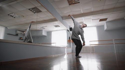 Le danseur professionnel répète à un miroir. Il fait les mouvements lisses et exacts. Ainsi, le