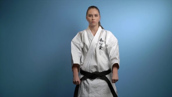 Thumbnail for A Woman in a Karate Greeting Pose Isolated on Blue