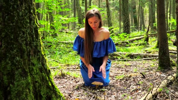 Thumbnail for A Woman in a Blue Dress Found a Big Mushroom Among Wild Forest. Mystical Mood.