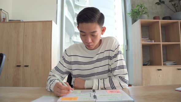 Young Asian Student Has Online Class Video Call in Classroom