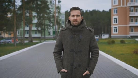 Thumbnail for Happy Dark-Haired Man with Beard in Brown Coat Walking Along the Street with Orange and Blue