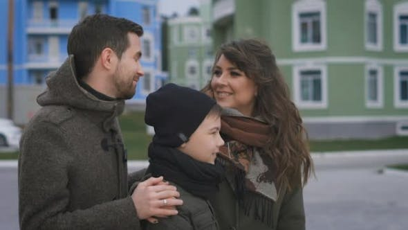 Thumbnail for Happy Young Family in Warm Clothing Standing Together on the Street Smiling