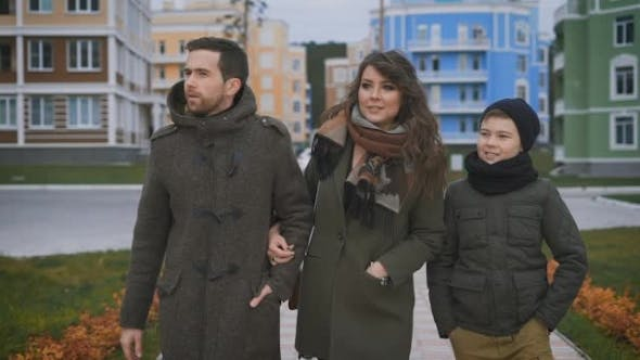 Thumbnail for Happy Young Family in Warm Clothing Are Walking Together on the Street Laughing and Talking