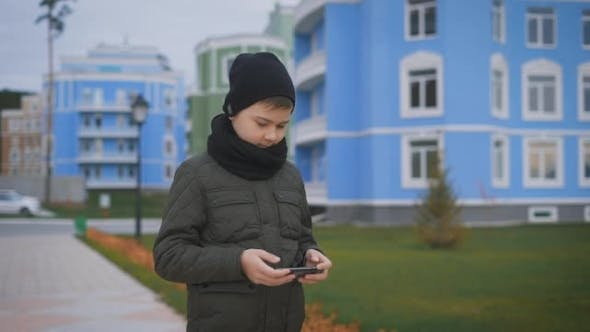 Thumbnail for Child in Warm Dark Grey Jacket and Black Cap and Scarf Playing Phone