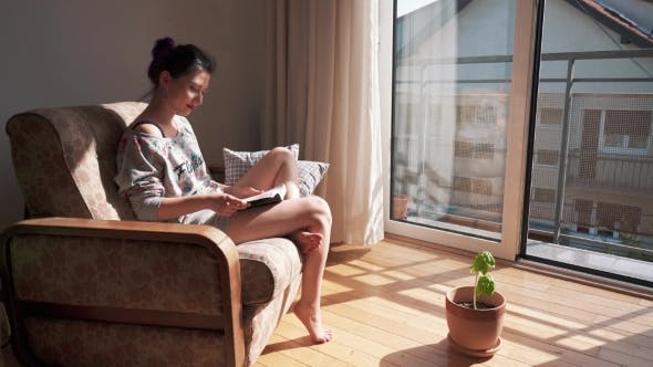 Thumbnail for Cute Girl Sitting By Opened Window Reading a Book