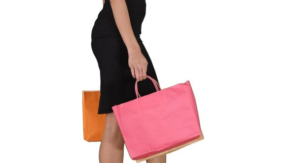Thumbnail for Young woman with shopping bags walking out from shop on