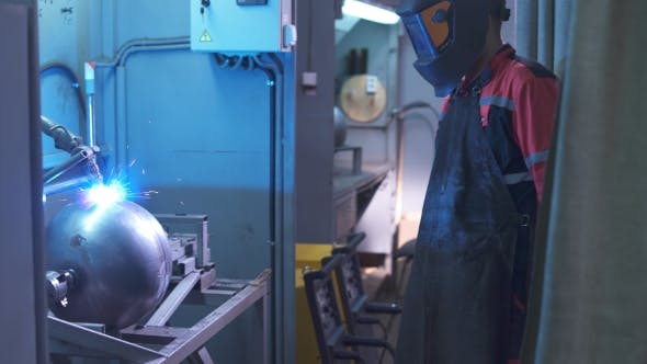 Thumbnail for An Employee in a Special Protective Suit Oversees the Process Works Welding Apparatus. Control the