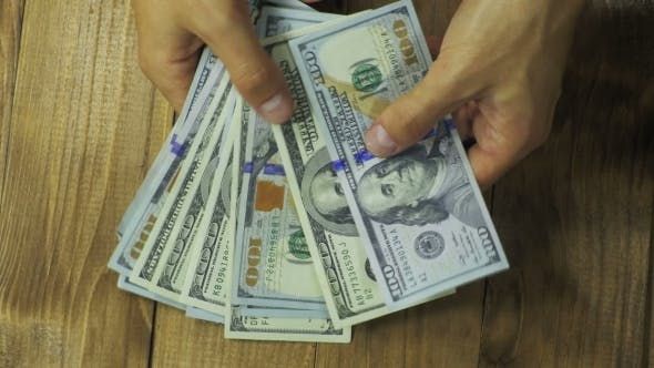 Thumbnail for Man Hands Consider Dollar Banknotes on a Wooden Table